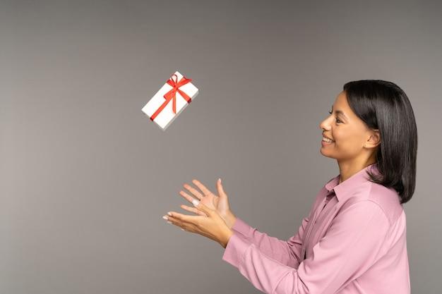 La donna felice vomita la confezione regalo per lo shopping a basso prezzo per i regali durante le festività natalizie sconti sulle vendite