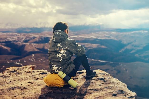 Turista felice si siede su uno zaino sullo sfondo di bellissime montagne