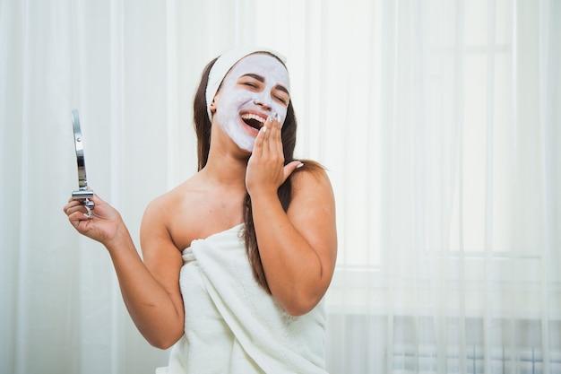 Donna felice in asciugamano e maschera facciale guardarsi allo specchio. trattamento di bellezza a casa. concetto di cura della pelle e ringiovanimento.