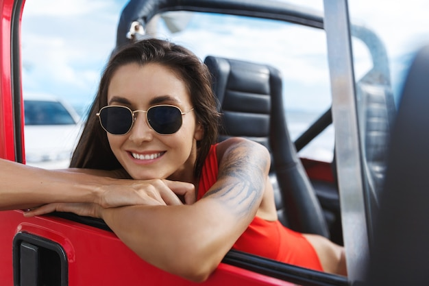 Viaggio di donna felice alla spiaggia in auto suv, seduto sul passeggero seduto in costume da bagno e occhiali da sole.