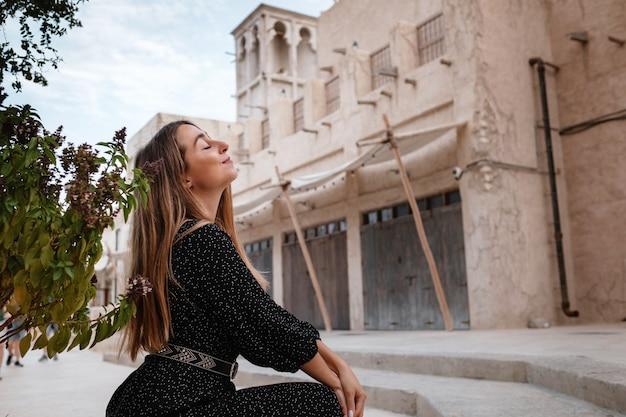 Felice donna viaggiatrice che indossa un abito nero che cammina per le strade di una vecchia città araba o villaggio nel mezzo del deserto. concetto di turismo e avventure ad al seef dubai