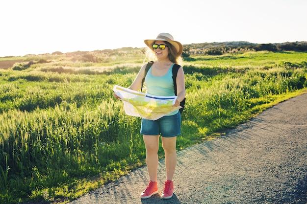 Felice donna viaggiatrice con zaino controlla la mappa per trovare indicazioni stradali