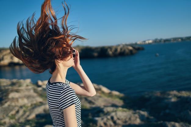 La maglietta della donna felice tocca i capelli sulla sua testa e si rilassa in montagna nella natura