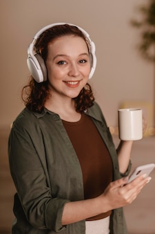 Donna felice che utilizza il suo smartphone e le cuffie a casa mentre beve il caffè