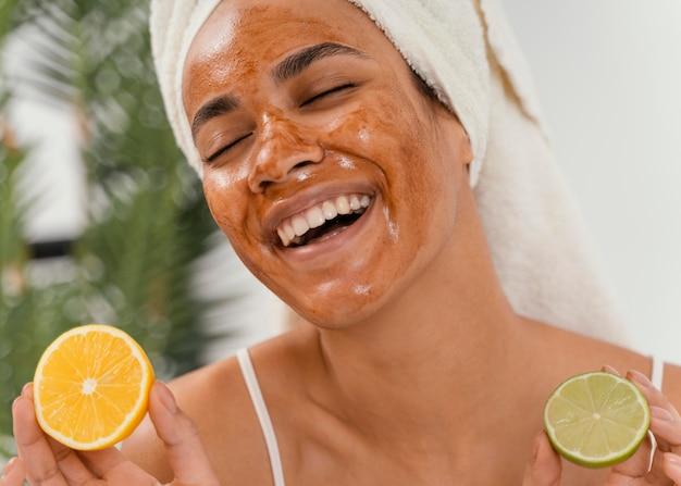 Donna felice che aspetta che la sua maschera per il viso faccia il suo effetto