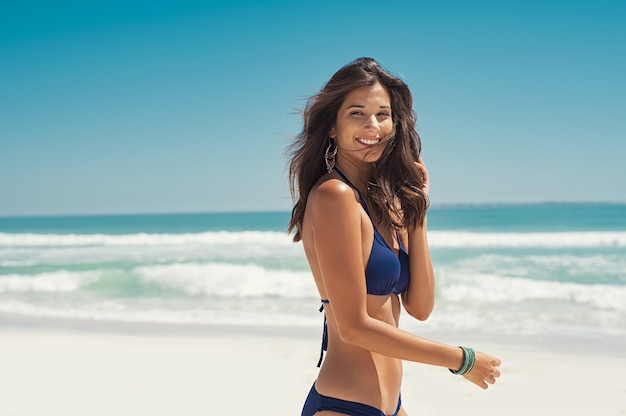 Donna felice che cammina sulla spiaggia