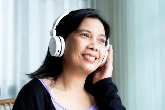 Donna felice che indossa la cuffia senza fili sopra l'orecchio bianco che ascolta la musica a casa