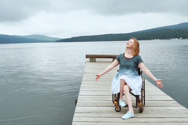 Donna felice in sedia a rotelle che si gode le vacanze al mare con le braccia aperte