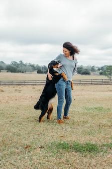 Donna felice con il cane attivo che gioca all'aperto allegro proprietario e grande bovaro del bernese si divertono sul campo contro il paesaggio del villaggio