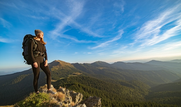 La donna felice con uno zaino da campeggio in piedi sulla montagna soleggiata