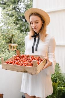 Donna felice con le ciliegie che indossa cappello e abito bianco.