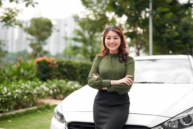 Donna felice con le braccia incrociate in piedi accanto alla sua auto