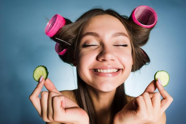 Donna felice con i bigodini sulla testa che tiene in mano dei cetrioli