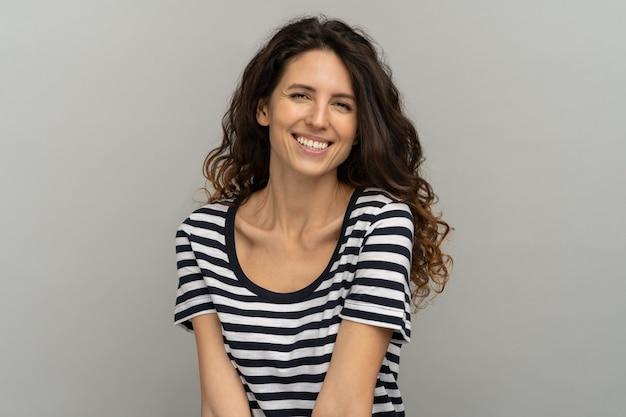 Donna felice con i capelli ricci e il sorriso a trentadue denti divertendosi, ridendo isolato su sfondo grigio di studio