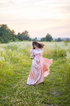 Donna felice con i capelli scuri che balla nel campo di fiori di campo e che tiene la parte inferiore del lungo abito rosa.