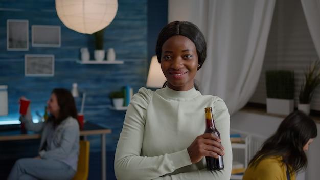 Donna felice con la pelle scura che beve birra divertendosi durante la festa
