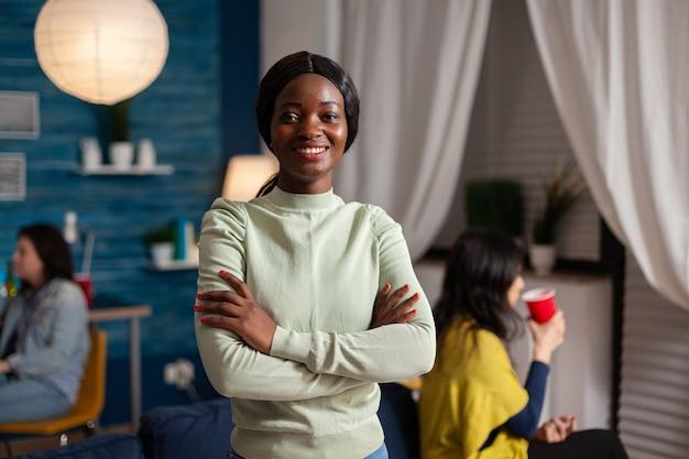 Donna felice con la pelle scura che si diverte durante la festa. in sottofondo amici multietnici che si riuniscono per festeggiare il compleanno a tarda notte in soggiorno.