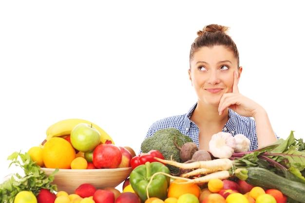 Una donna felice con frutta e verdura su sfondo bianco