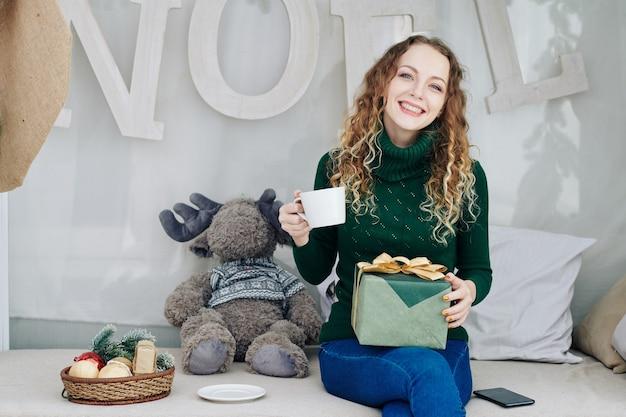 Donna felice con regalo e tazza di tè