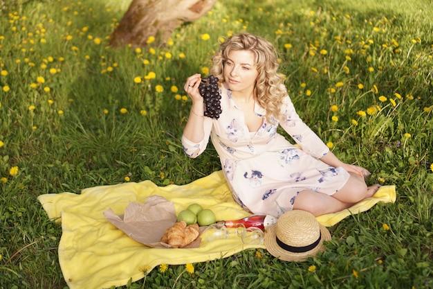 Donna felice con l'uva a un picnic nel giardino estivo