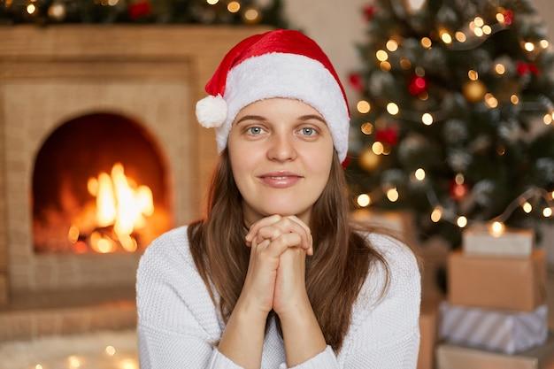 Donna felice con le mani sotto il mento guardando direttamente la fotocamera con un sorriso, indossando un maglione casual e cappello di babbo natale, seduto vicino all'albero di natale decorato con ghirlanda e camino.