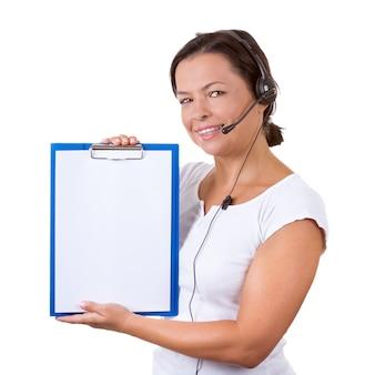 Donna felice con auricolare che lavora al callcenter tieni gli appunti con carta bianca per i tuoi segni e design su uno sfondo bianco