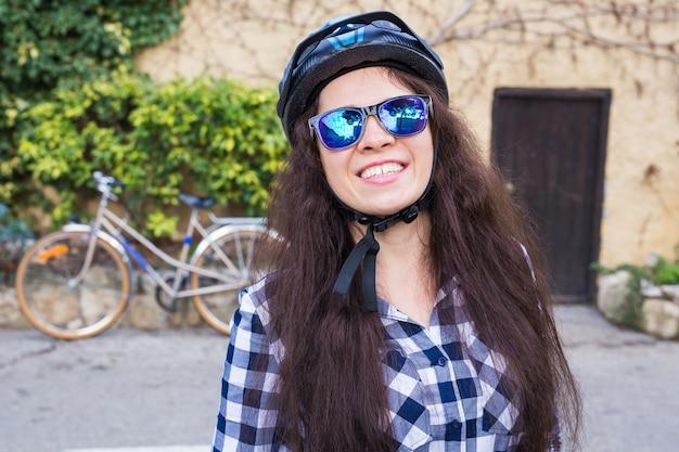 Donna felice con casco e occhiali da sole in posa contro la bicicletta e la strada