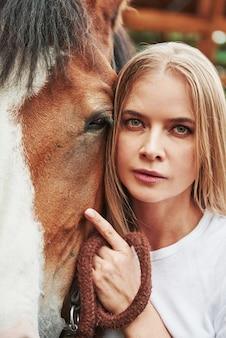 Donna felice con il suo cavallo nel ranch durante il giorno.
