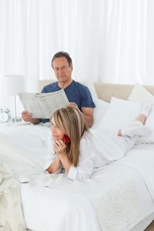 La donna felice con lei è aumentato mentre il suo marito sta leggendo un giornale
