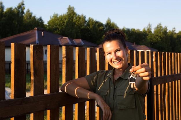 Donna felice con le chiavi di casa in mano vicino alla staccionata di legno della sua casa in un villaggio di cottage