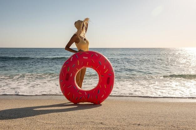 Donna felice con ciambella gonfiabile su una spiaggia tropicale