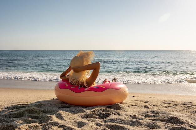 Donna felice con ciambella gonfiabile su una spiaggia tropicale.