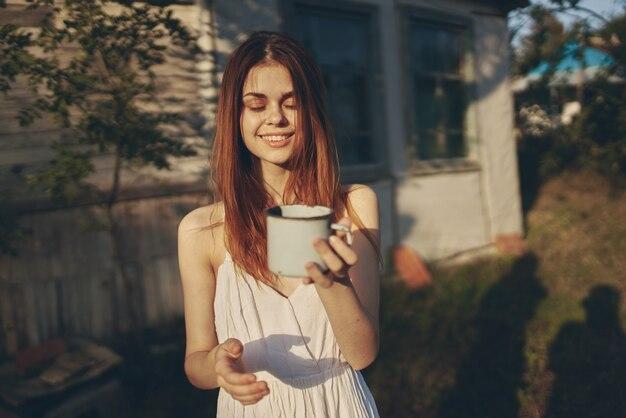 Donna felice con la tazza di ferro all'aperto nel giardino vicino a edificio leggero.