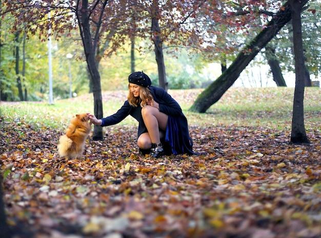 La donna felice con capelli ricci lunghi tiene il piccolo cane. la bella ragazza abbraccia il cagnolino. signora con cucciolo. donna attraente sorridente con il cane di pomerania. ragazza con cane in mano. adozione di animali domestici, vita di animali domestici.