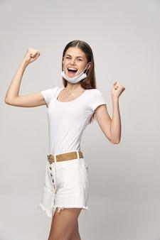 Donna felice con una mascherina medica e tiene le mani in un pugno