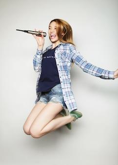Donna felice con microfono che salta e canta Foto Premium