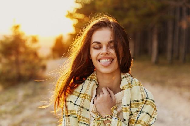 La donna felice con un plaid differisce dalla lingua e dalla natura del tramonto della foresta degli alberi