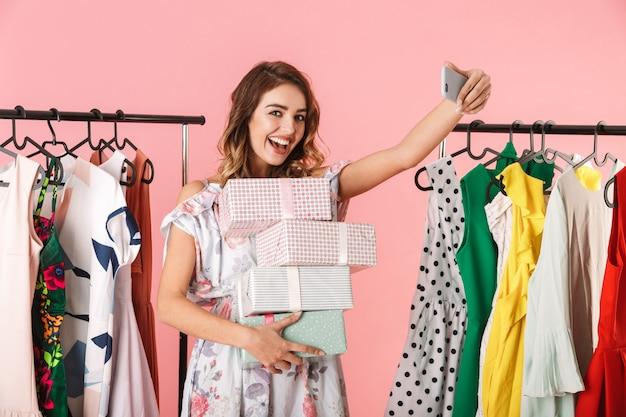 Donna felice con acquisto in piedi in negozio vicino a stendibiancheria e tenendo selfie sul telefono cellulare isolato in rosa