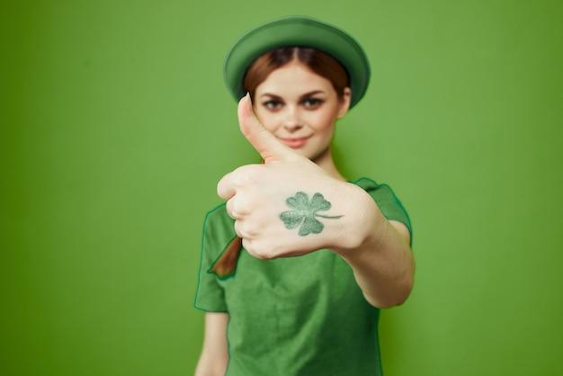 Donna felice con l'acetosella il giorno di san patrizio in abiti verdi
