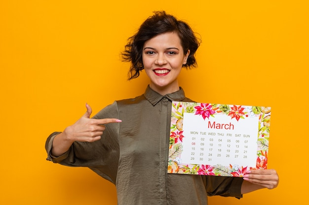 Donna felice con i capelli corti che tiene il calendario cartaceo del mese di marzo che punta con il dito indice su di esso sorridendo allegramente celebrando la giornata internazionale della donna l'8 marzo in piedi su sfondo arancione