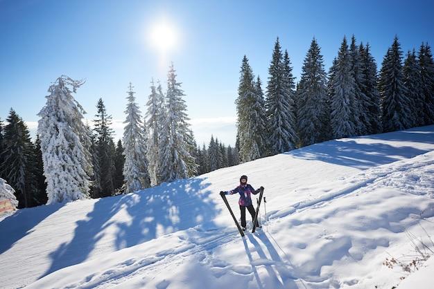 Donna felice con lo sci in piedi nel mezzo del pendio di montagna innevato