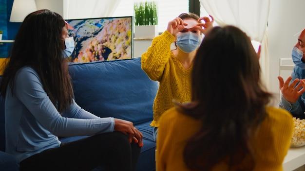 Donna felice con una nota adesiva sulla fronte che gioca a nome con amici multietnici mantenendo le distanze sociali bevendo birra nel soggiorno di casa a causa della pandemia sociale. persone che si divertono durante l'epidemia