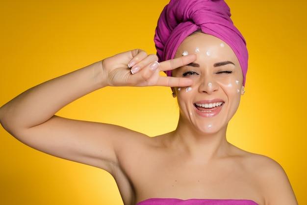 Donna felice con l'asciugamano in testa dopo la doccia ha applicato la crema sul viso