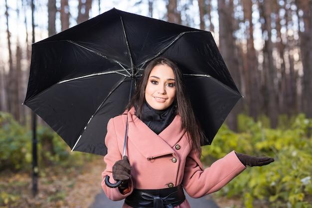 Donna felice con l'ombrello sotto la pioggia durante la passeggiata nella natura autunnale