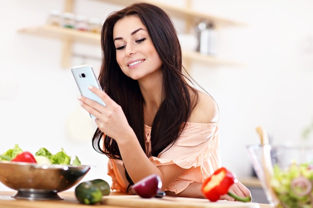 Donna felice con verdure in cucina moderna