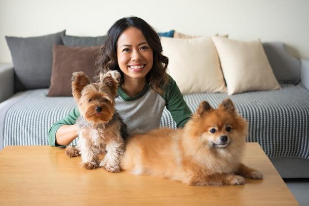 Donna felice con yorkie e spitz dogs a casa