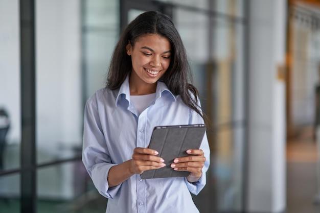Donna felice che lavora con gadget moderni in ufficio