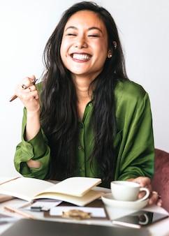 Donna felice che scrive un diario nel suo ufficio