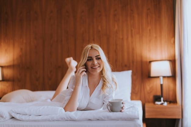 Donna felice che usa un telefono cellulare mentre è sdraiata sul letto e beve il caffè del mattino a casa