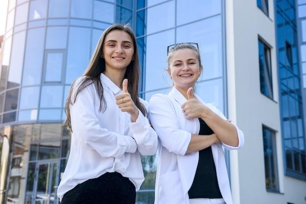 Donne felici in giacca e cravatta con cartella in piedi davanti all'ufficio di grandi imprese